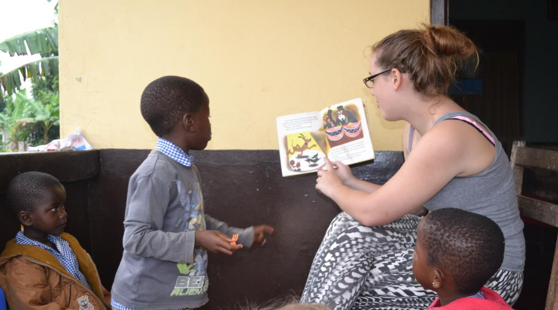 Voluntaria leyendo un libro a niños durante su trabajo voluntario en Ghana.